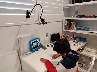 A kid in a virtual art class, using the Classnika app to communicate with his teacher
